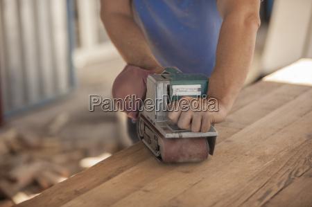 carpenter using wood sander