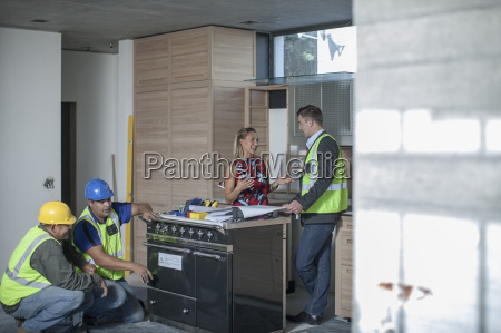 architect and woman discussing kitchen furnishing