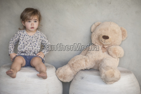 serious baby girl and teddy bear