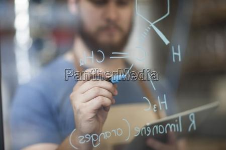 man writing formula on glass pane