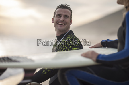 man smiling at woman with surfboard