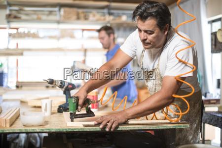 man drilling frames in canvas workshop