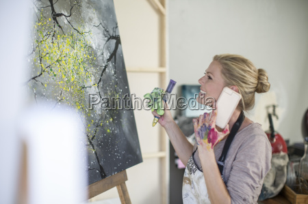 female painter in front of canvas