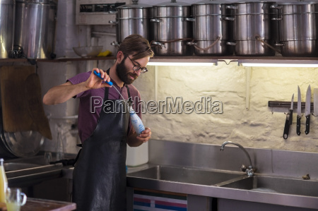 man cleaning glass bottle with a