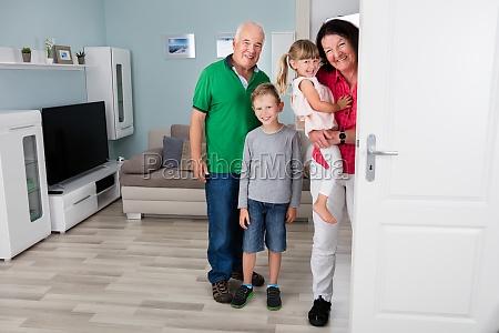 grandparent and grandchildren standing behind door