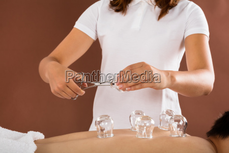 therapist giving cupping therapy to man