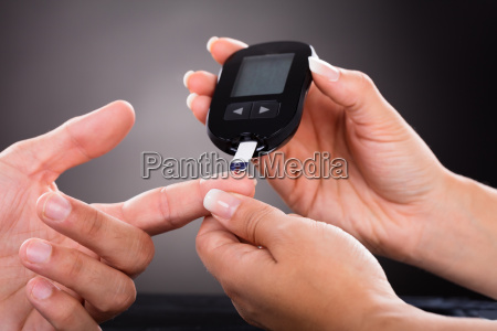 doctor checking patients sugar level with