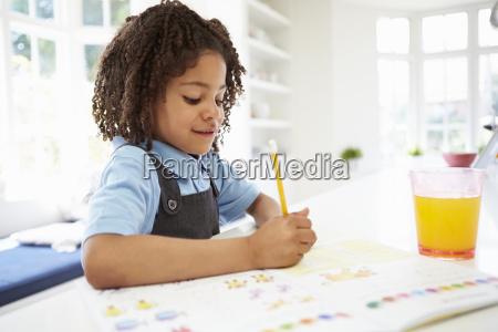girl in school uniform doing homework