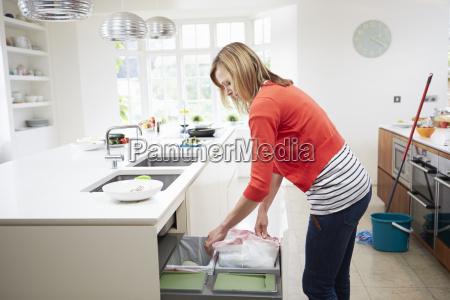 woman standing in kitchen emptying waste