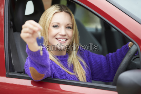 teenage girl standing next to car