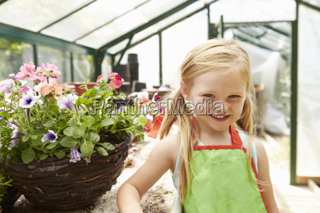girl growing plants in greenhouse