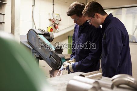 engineer teaching apprentice to use grinding