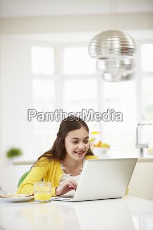 hispanic girl using laptop eating breakfast