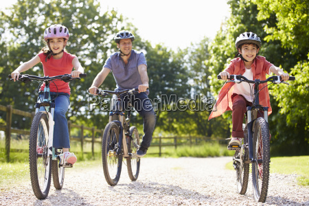 hispanic father and children on cycle