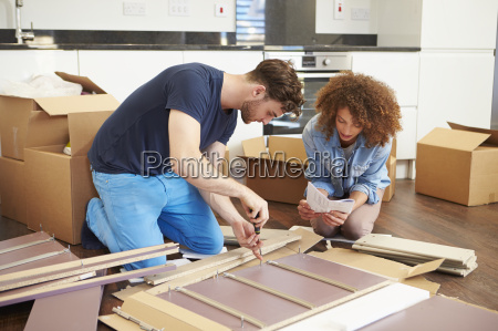 couple putting together self assembly furniture