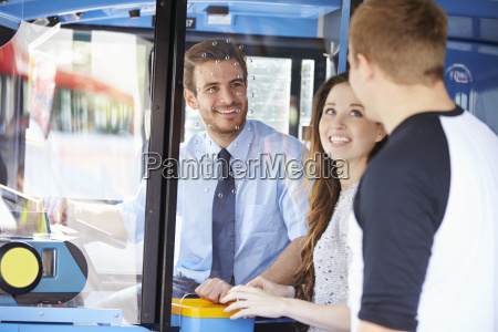 young couple boarding bus and buying