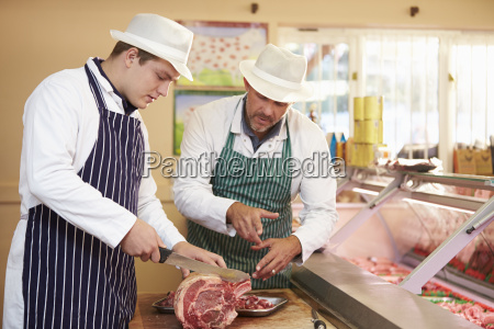 butcher teaching apprentice how to prepare