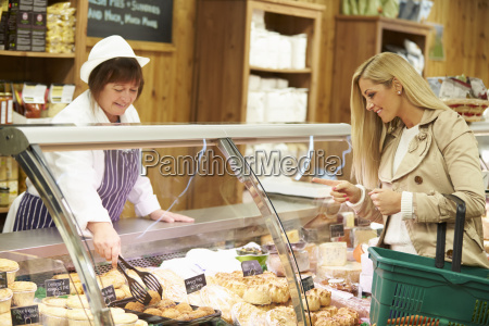 female sales assistant serving customer in
