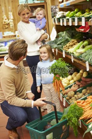 family choosing fresh vegetables in farm