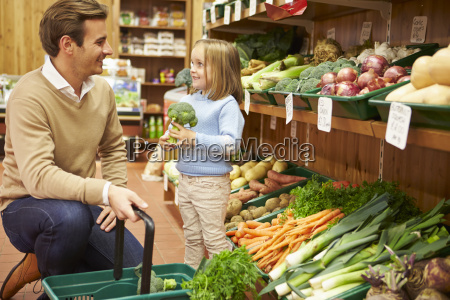 father and daughter choosing fresh vegetables