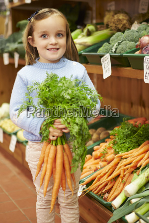 young girl holding bunch of carrots