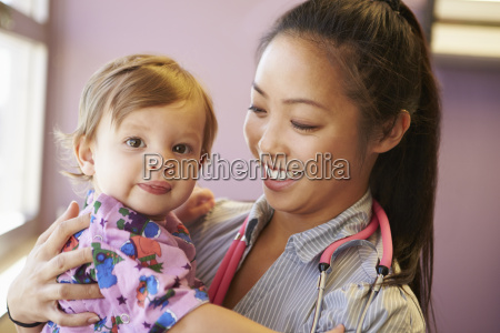 young girl being held by female