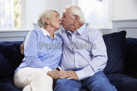 affectionate senior couple sitting on sofa