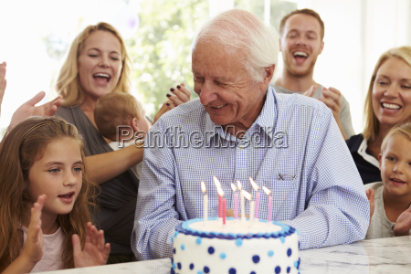 grandfather blows out birthday cake candles