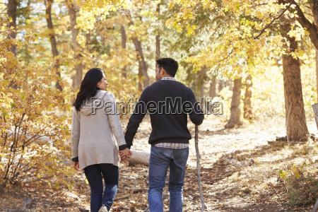 hispanic couple hold hands hiking in