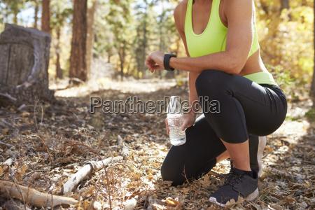 female runner kneels in forest looking