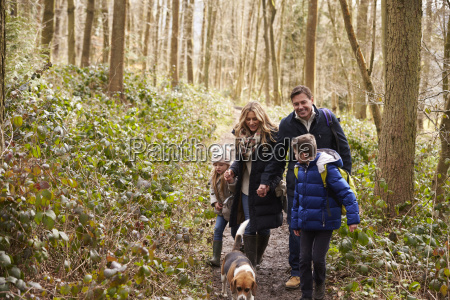 family and dog walk in a
