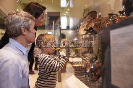 family looking at artifacts in glass