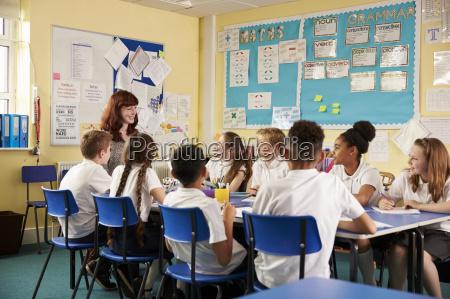 school teacher and kids work on