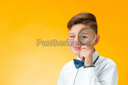 little boy using magnifier looking close