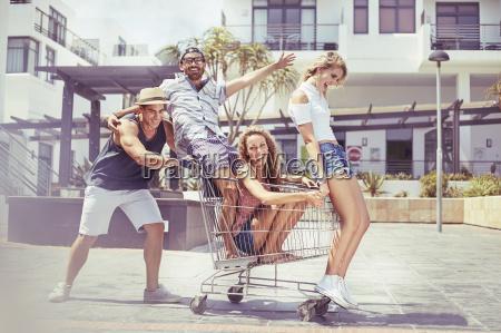 portrait playful friends riding shopping cart
