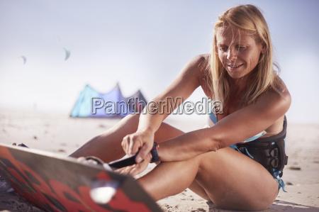 woman fastening kiteboard to feet on