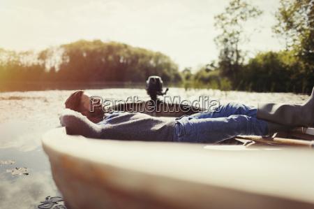 serene man laying relaxing in canoe