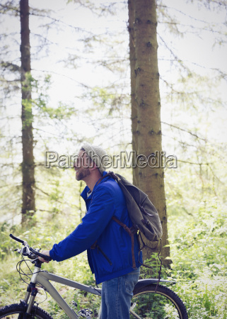 man with backpack and mountain bike