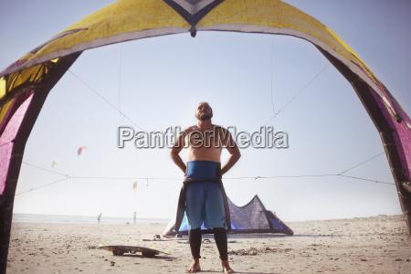 man, preparing, to, kiteboard, on, sunny - 19400196