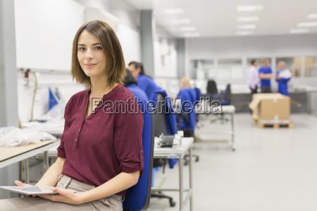 portrait confident businesswoman with digital tablet