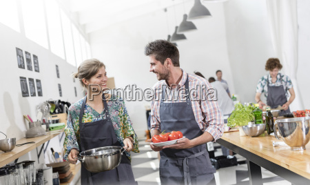 couple carrying food in cooking class