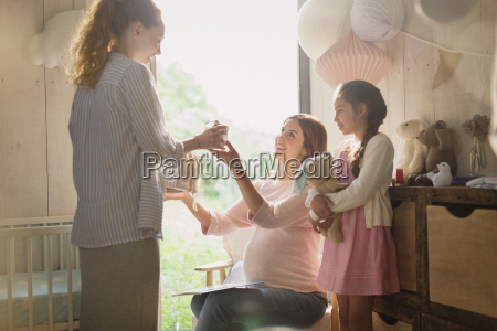pregnant woman receiving gift in nursery