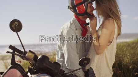 affectionate young couple at motorcycle with