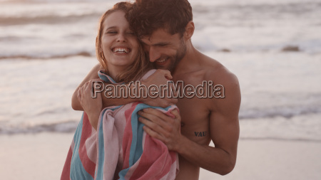 affectionate young couple hugging on beach
