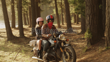young couple riding motorcycle in woods