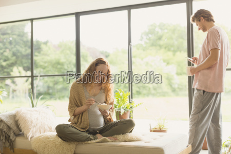 pregnant couple eating and drinking coffee