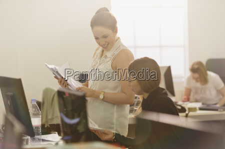 businesswomen discussing paperwork at computer in