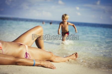 son running toward mother sunbathing on