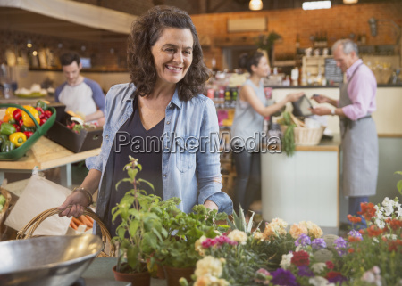smiling woman shopping for flowers in