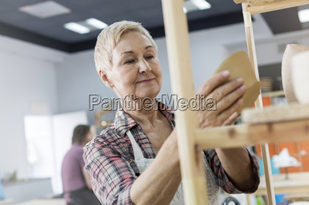 smiling senior woman placing pottery on